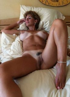 Tanned milf lady on the bed -..